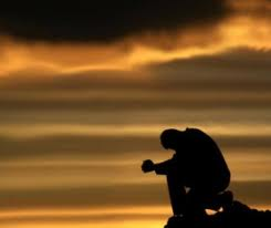 A man in prayer during sunset